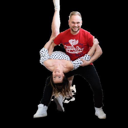 Mies ja nainen tanssii ja mies taivuttaa naista